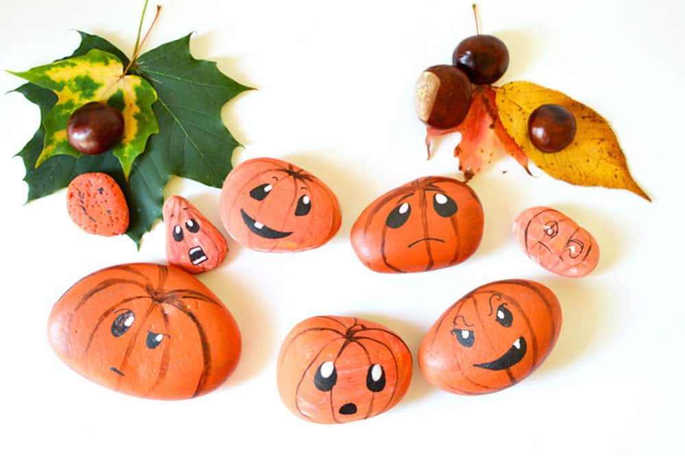 Painted pumpkin rocks with different emotions on their faces.