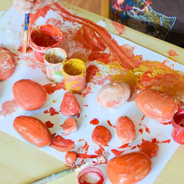Rocks painted with orange, yellow and white paint.