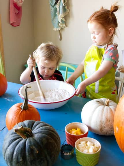 One child holds a bowl of baking ingredients while I second child stirs with a wooden spoon.