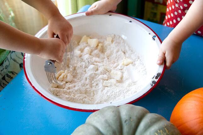 Two children mix butter into the flour mixture.