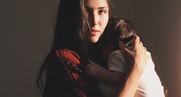 a mother holds her baby