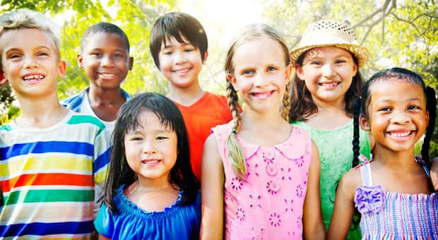 A group of diverse children smiling at the camera.