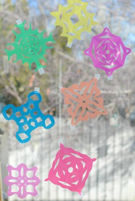 Green, yellow, purple, blue, pink, red and orange snowflakes taped to a window