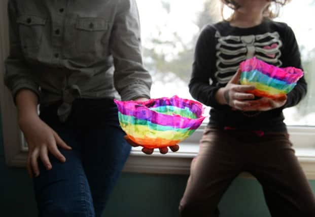 Two school-aged kids holding their finished rainbow papier mâché bowls.