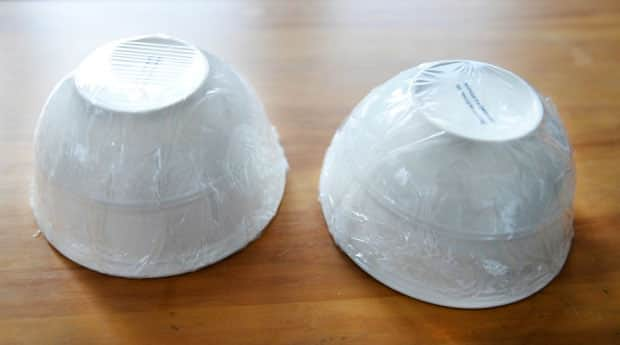 Two bowls, sides covered with plastic wrap and sitting upside down on a table.