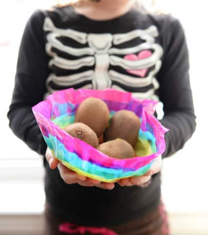 A girl holding a finished rainbow bowl, filled with kiwis.