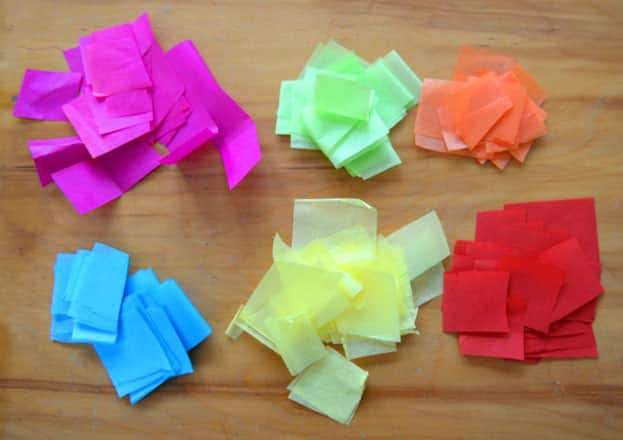 Six piles of different coloured tissue paper, cut into squares.