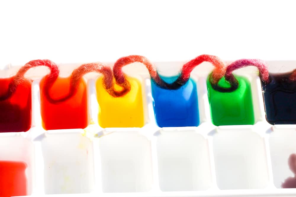 An ice cube tray filled with colourful water.