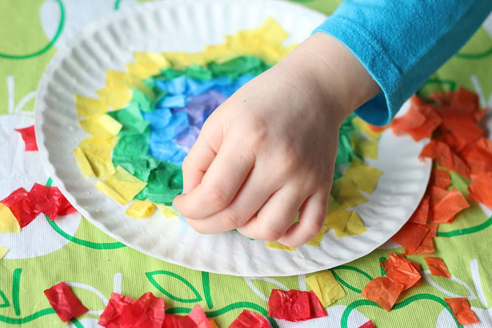 A child glues tissue paper to a paper plate.