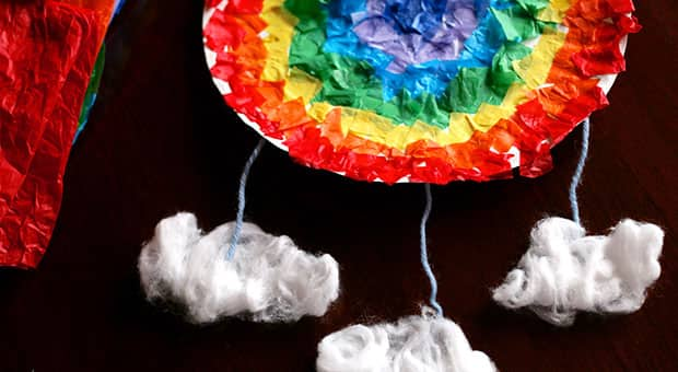 Tissue-paper squares glued to a paper plate in a circular rainbow pattern, with cotton-ball clouds hanging from the plate by string.