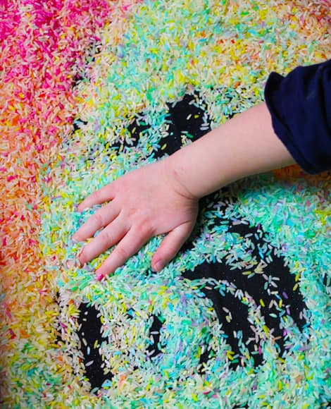 A hand playing with rainbow rice.