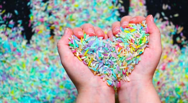 A child's hands holding a pile of rainbow rice.