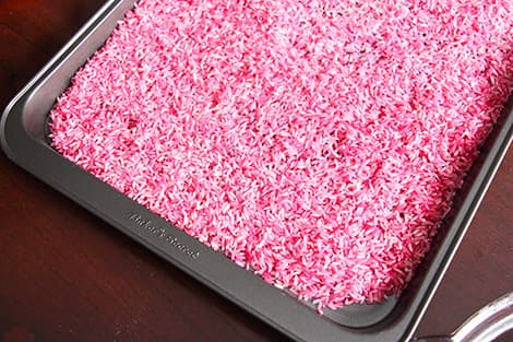 A baking sheet with pink rice, drying.