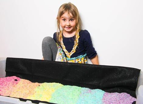 A happy little girl next to the bin of rainbow rice.