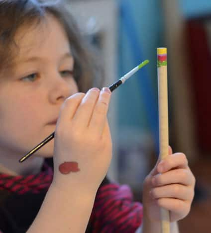 A girl paints a wand.