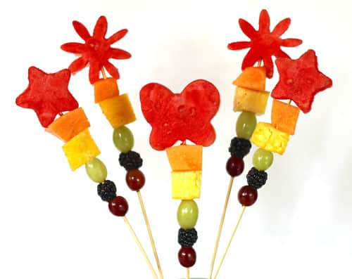 Rainbow fruit wands with watermelon shape cut-outs at the top of each wand.