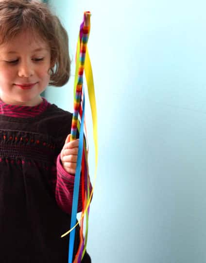 A girl holds her rainbow wand.