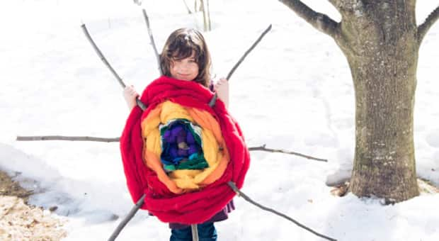 A girl standing with a giant rainbow wheel, woven out of sticks and colourful material (old t-shirts, roving, fabric, etc.).