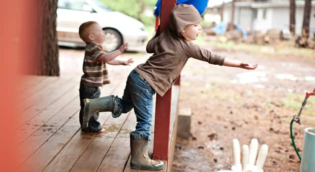Two kids are exploring the rain beyond their camp site