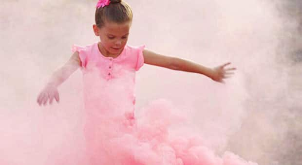 A girl in a pink shirt with a pink bow in her hair dancing in a cloud of pink smoke.