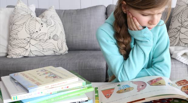 a young girl is bracing herself before she tucks into a stack of books nearby