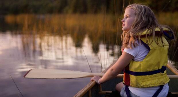 A calm, contemplative girl in a canoe, wearing a lifejacket.