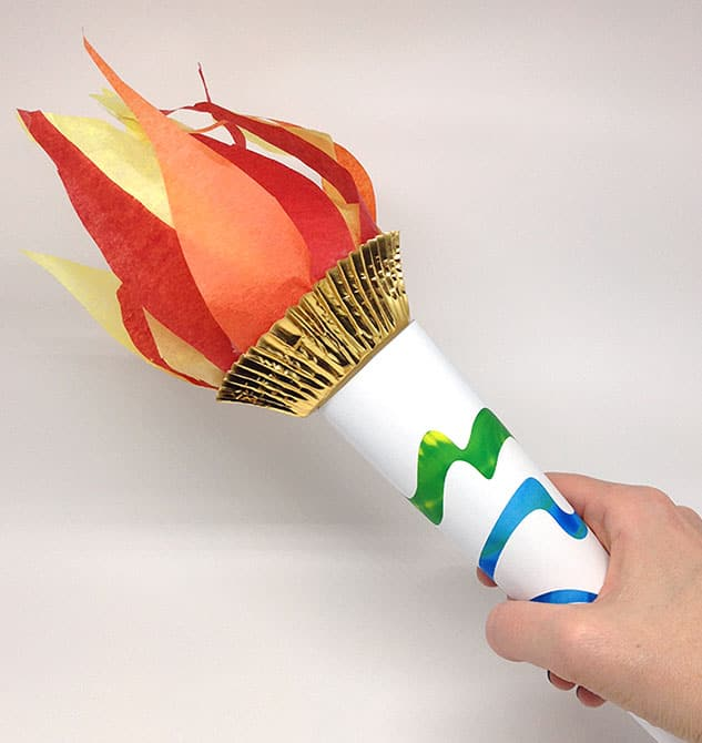 Hand holding a finished paper torch.