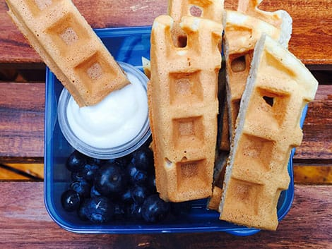 A container with waffle sticks and a small tub of yogurt.