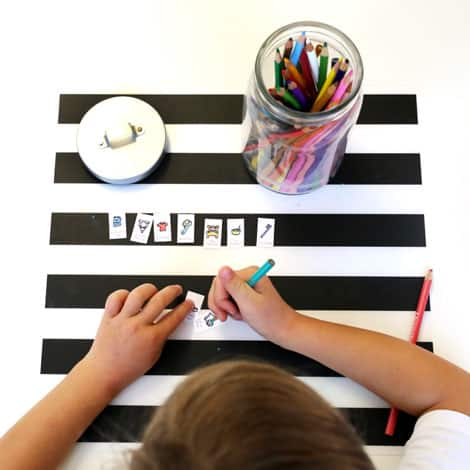 A young child colouring all of the images on the routine-jar sticks.
