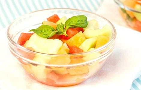 A bowl of melon and cucumber, topped with a sprig of basil leaves.