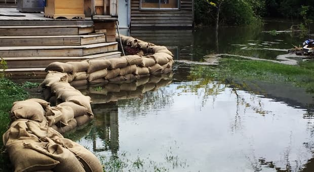 bags of sand lining a lake near a house