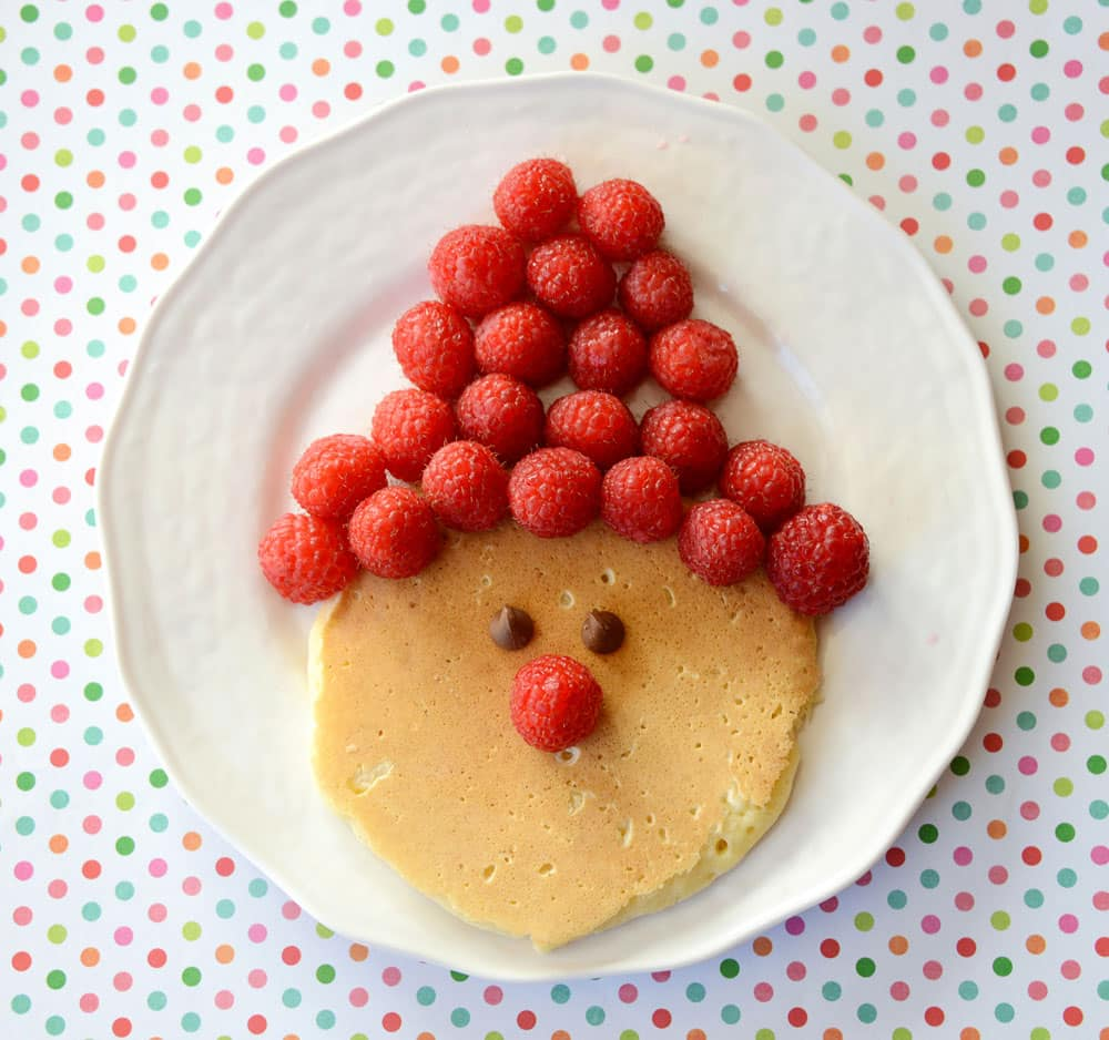 A pancake with raspberries in the shape of Santa's hat above.