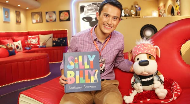 Bookaboo sitting with Patrick Chan and a copy of Silly Billy by Anthony Browne.