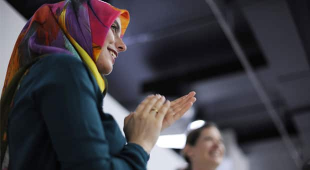 Two women smiling and clapping at a meeting.