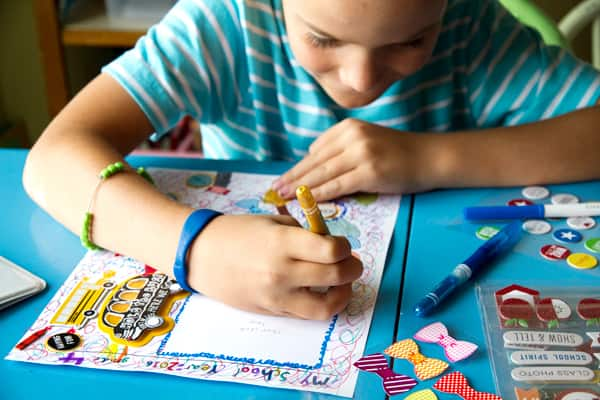 A child draws the title page of their memory book.