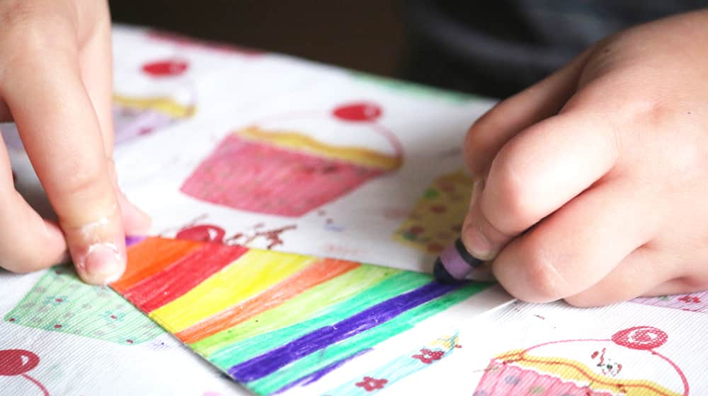 A child colours bright stripes on a piece of paper with crayons.