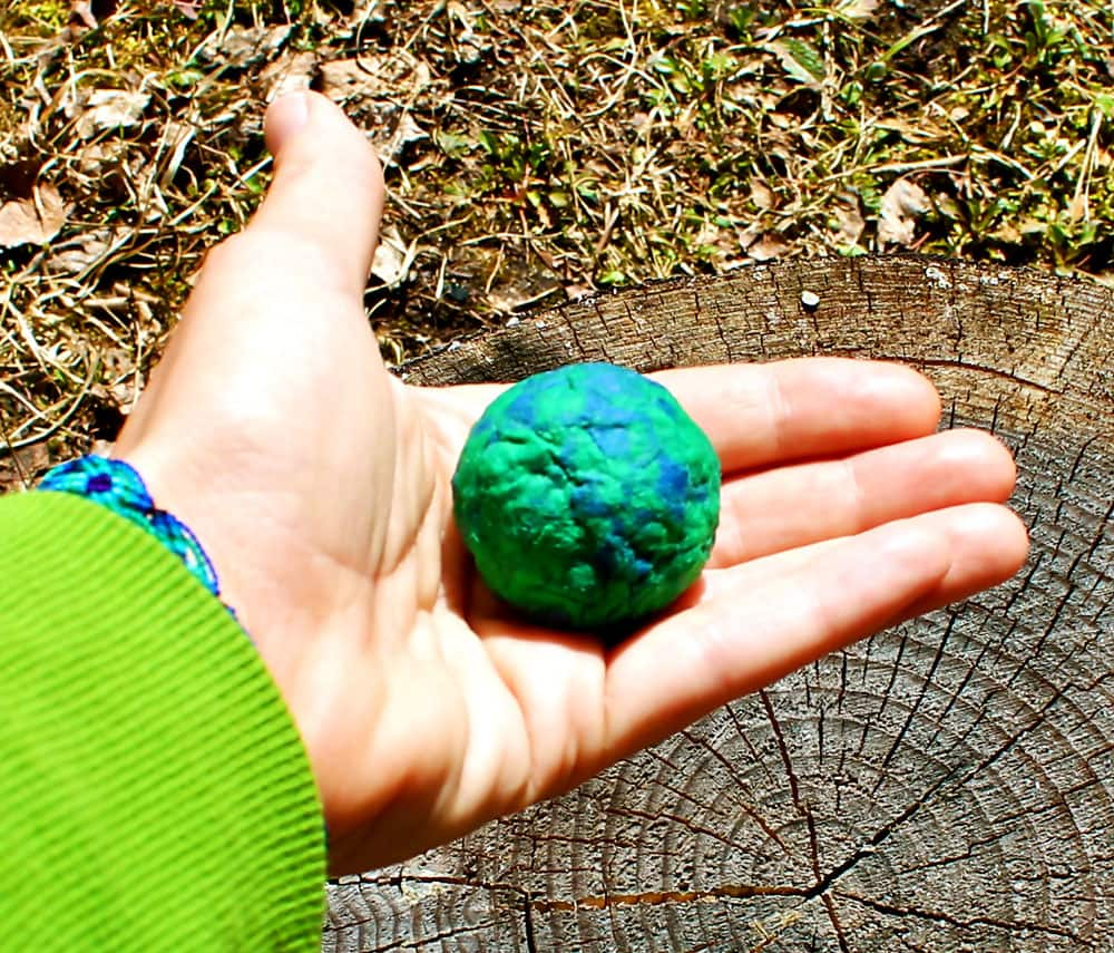 A round seed bomb sitting in the palm of a hand. It's about the size of a plum.
