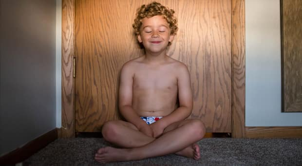 a child calmly meditates alone in his bedroom