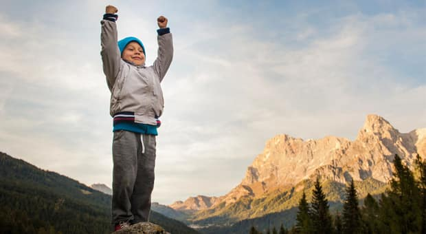 A child on top of a mountain looking proud