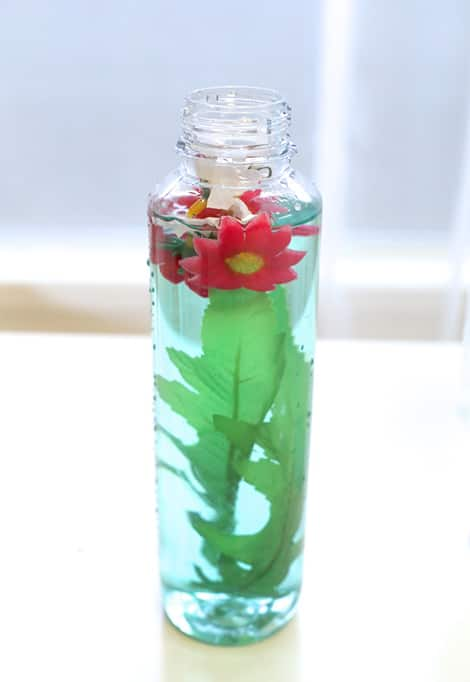 Finished spring sensory bottle, filled with faux flowers and leaves.