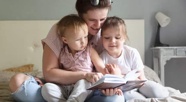 A woman reading to her children