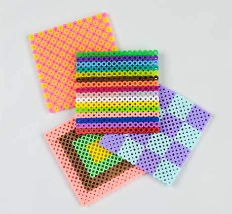 Four coasters stacked with varying colours and designs.