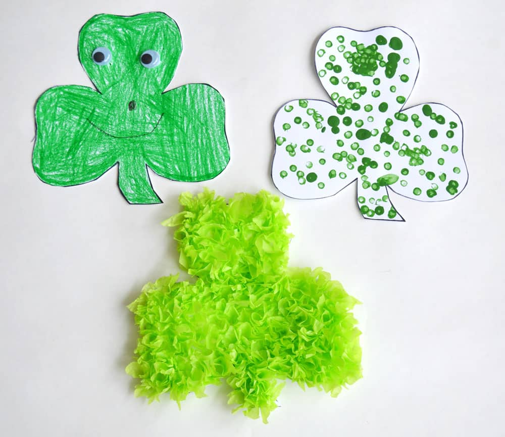Three shamrocks, one coloured with a green crayon with googly eyes and a smiley face; one covered with green dots; one covered with bright green tissue paper.