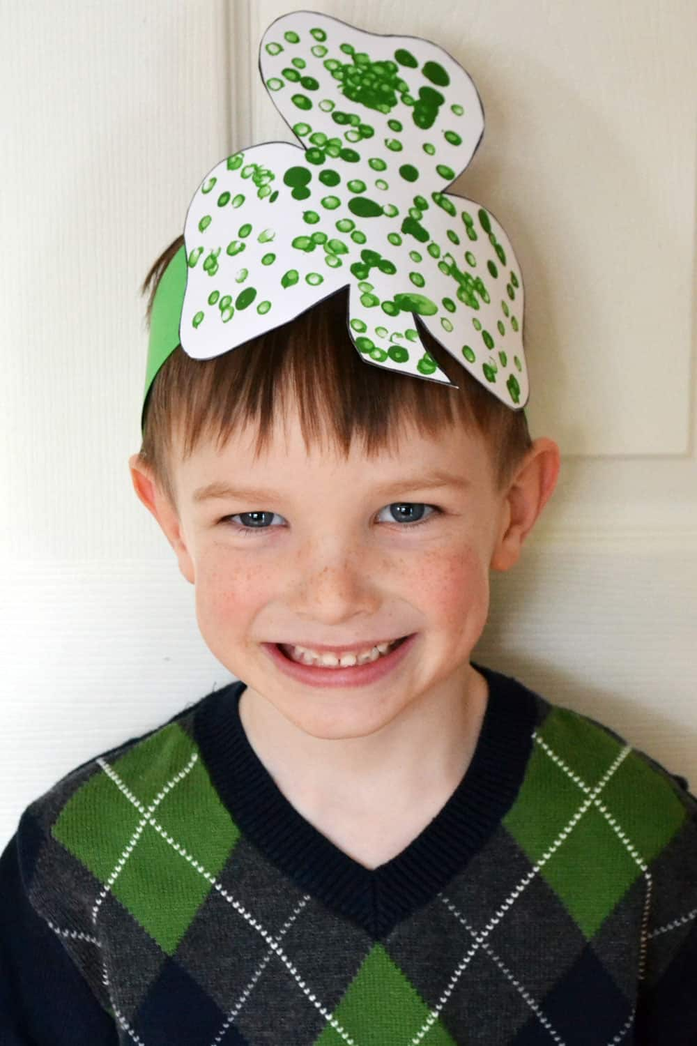 A smiling boy wearing a headband with a cut-out shamrock shape on it.