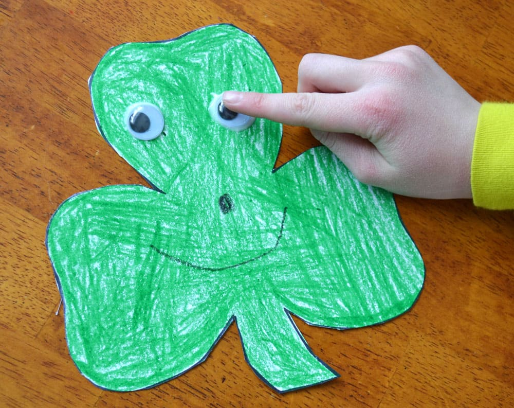 A child pressing a googly eye onto a green shamrock coloured with green crayons.