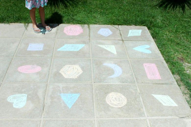 A piece of sidewalk covered in shapes drawn with sidewalk chalk.