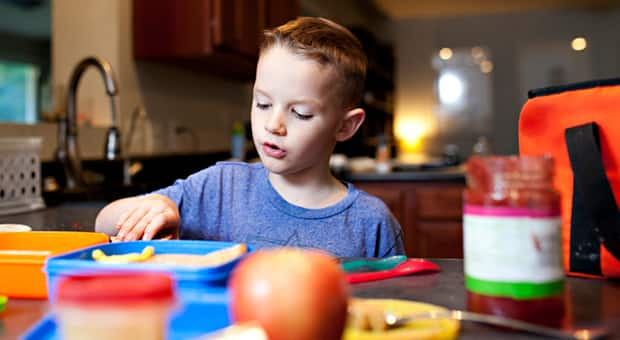 Child preps their own lunch.