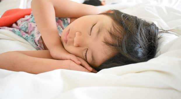 a young child sleeps soundly in bed