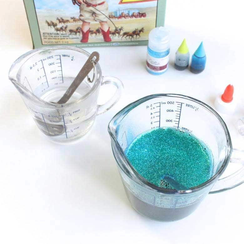 Two measuring cups, one with water and one with turquoise sparkles.