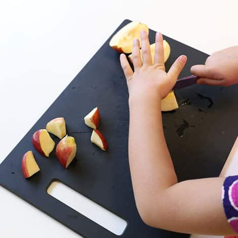 child cutting apples into pieces on a cutting board with a butter knife